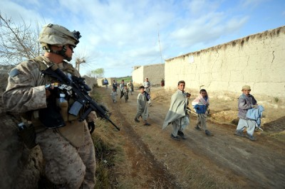 Afghan children walk past a US Marine of