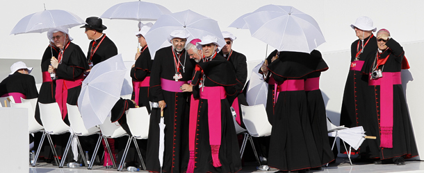 Bishops stand with white umbrellas on a