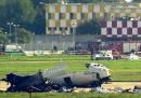 Il deposito bagagli dell'aeroporto di Linate, dietro l'aereo di linea della Sas, in primo piano, dopo l'incidente dell'8 ottobre 2001 (AP Photo/Luca Bruno)