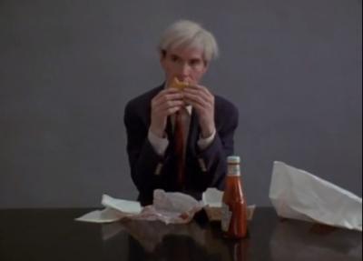 Andy Warhol che mangia un hamburger