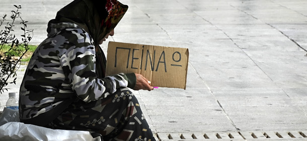 A woman holds a cardboard reading in Gre