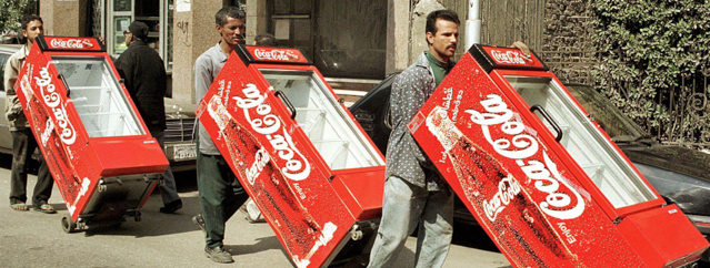 Egyptian workers push Coca Cola refrigerators thro