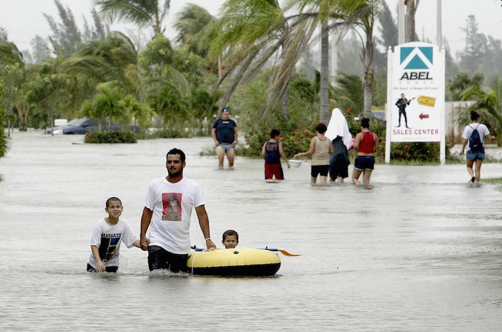 Mark Balencourt (C) uses a raft to ferry
