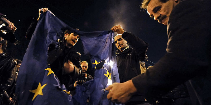 Demonstrators burn an EU flag near the E