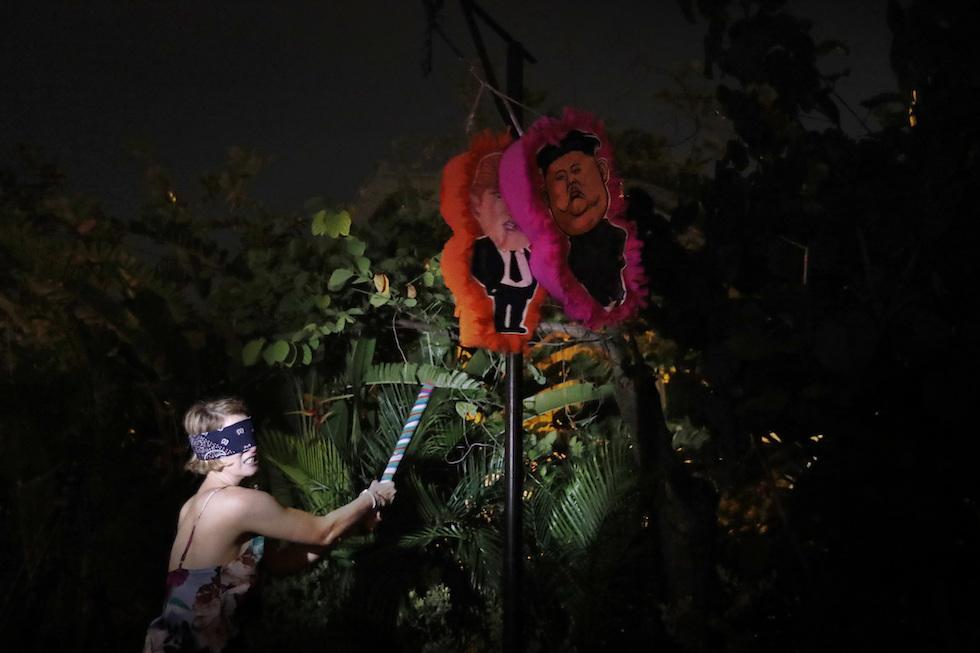 Una donna colpisce lepiñatas ispirate a Trump e Kim a Singapore l'8 giugno 2018